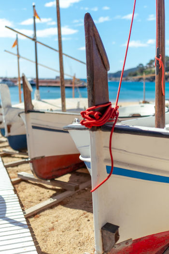 Sailboat moored on wooden post at beach against sky