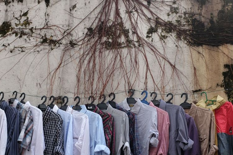 Shirts hanging on clothesline for sale against wall