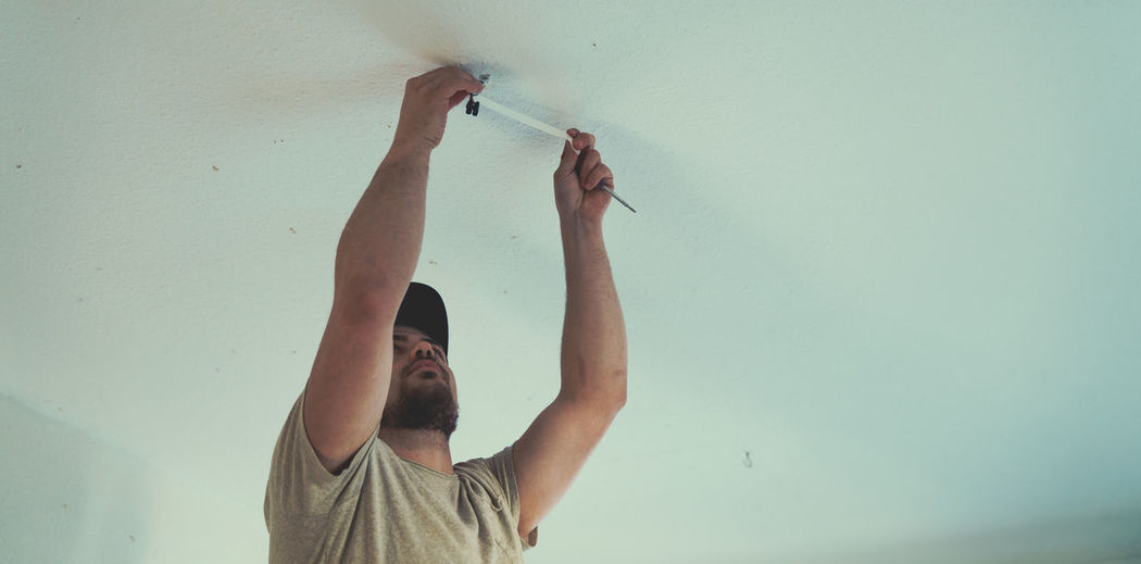 Low angle view of man repairing ceiling at home