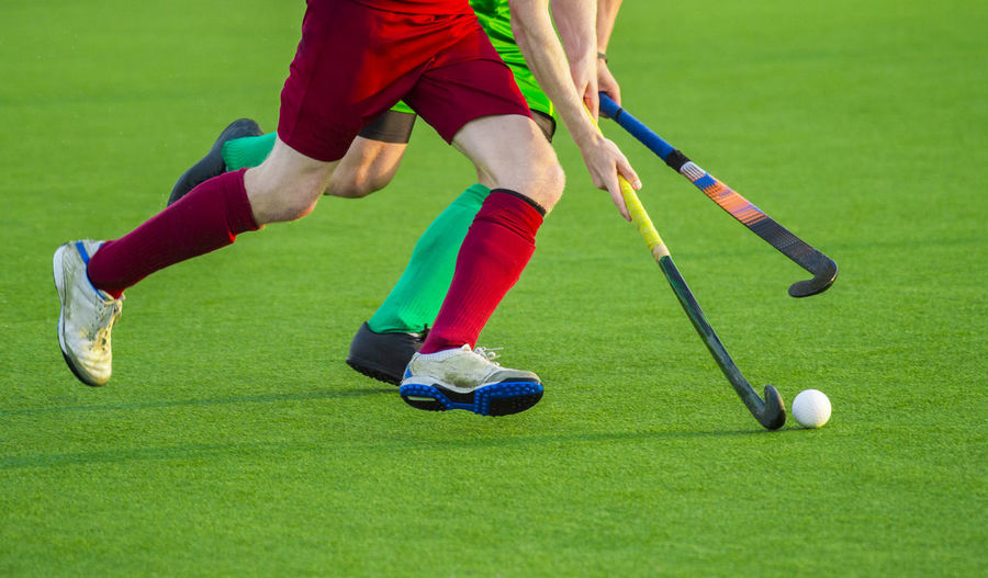 Close up of two field hockey players, challenging eachother for the control and posession of the ball during an intense, competitive match on professional level Field Hockey Fight Grass Green Man Activity Ball Club Day Grass Green Color Leisure Activity Motion Nature One Person Paly Plant Players Playing Shoes Sport