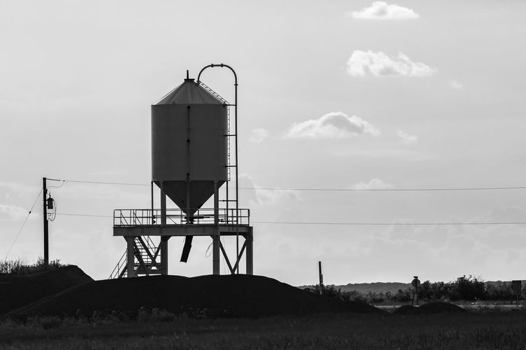 Low angle view of water tower on land against sky