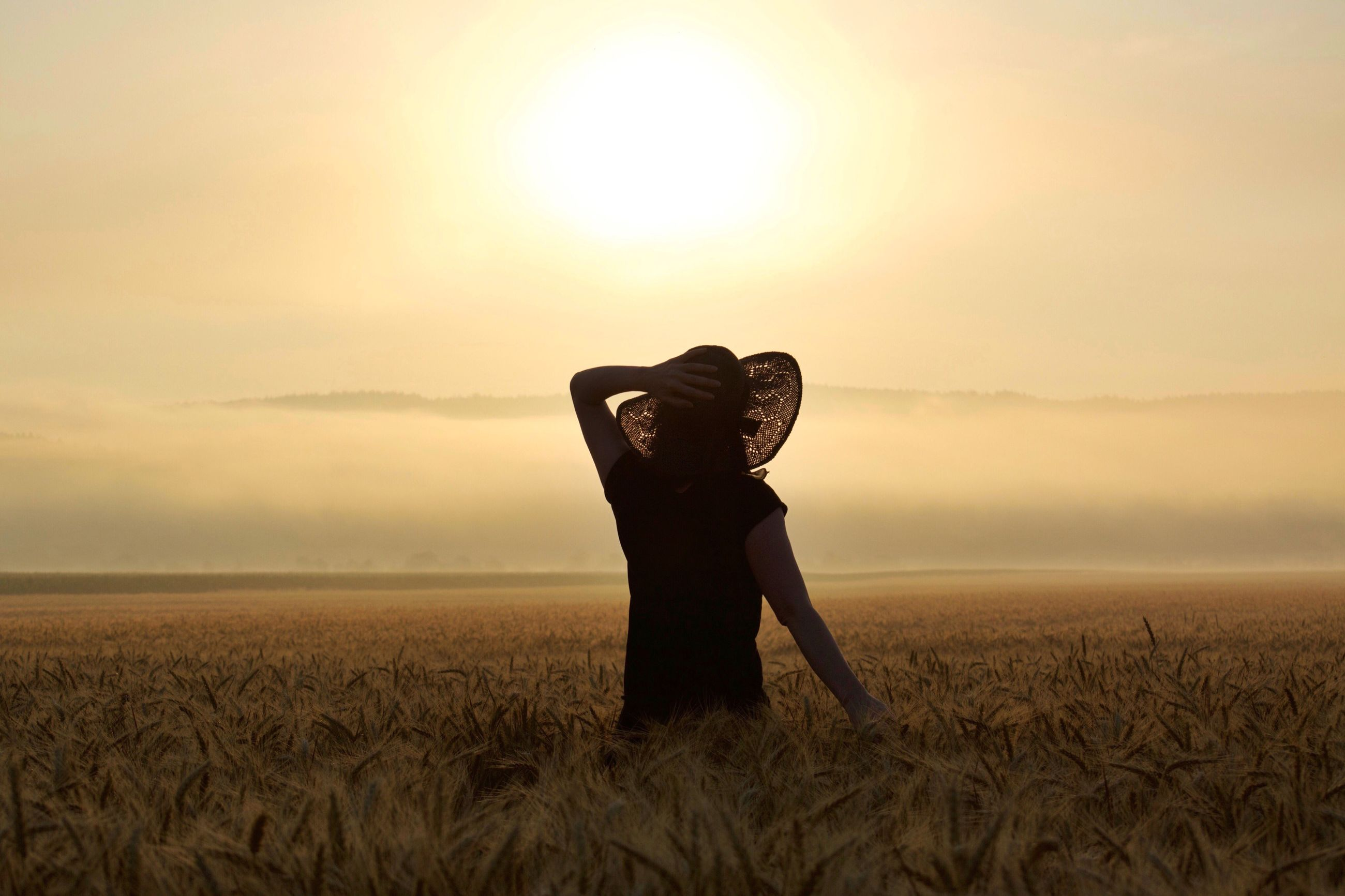 field, sky, nature, one person, leisure activity, sunset, outdoors, lifestyles, beauty in nature, scenics, real people, landscape, agriculture, growth, day, grass, young women, standing, women, young adult, people