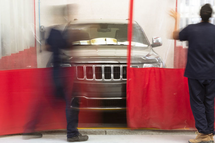 Blurred motion of man and red car in city