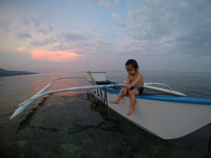 Row your boat One Person Pointing Boy Child Childhood Outrigger Child Sitting On A Boat Ocean Child Horizon Dusk Sea Ocean Boat Smiling Holding Canoe Outrigger Sailing Boat