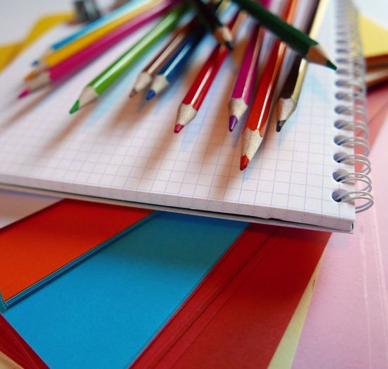 Close-up of colorful pencils on spiral notebook