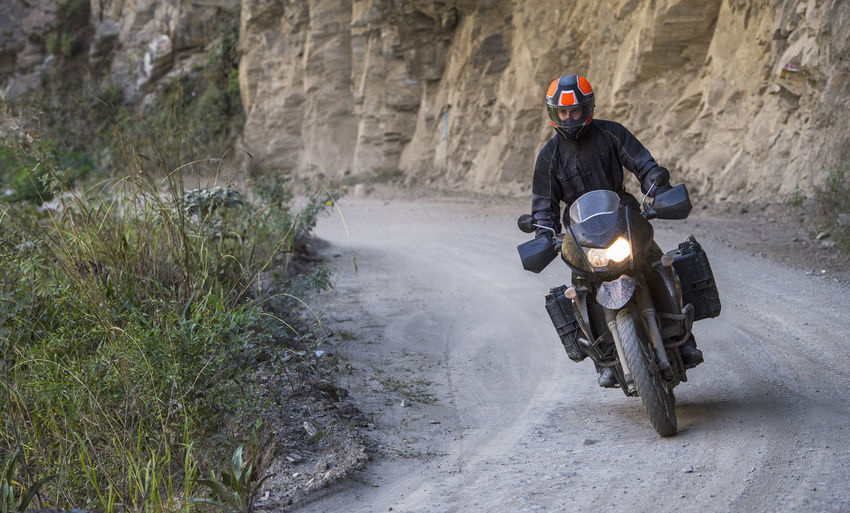 Rear view of person riding motorcycle on road