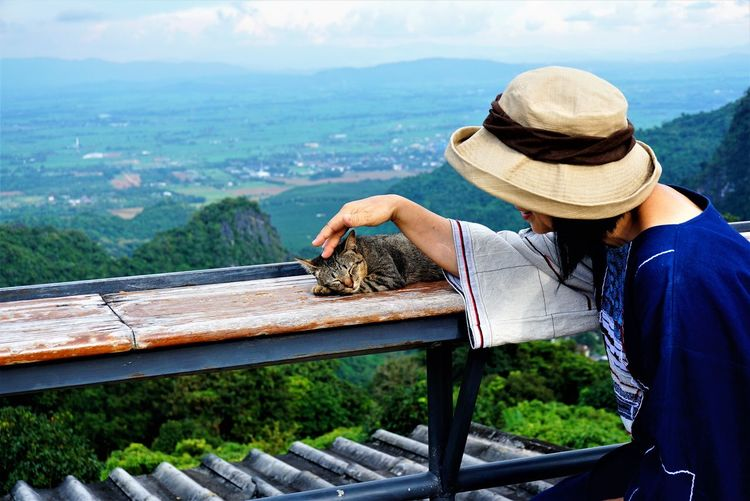 Woman touching domestic cat while standing against railing