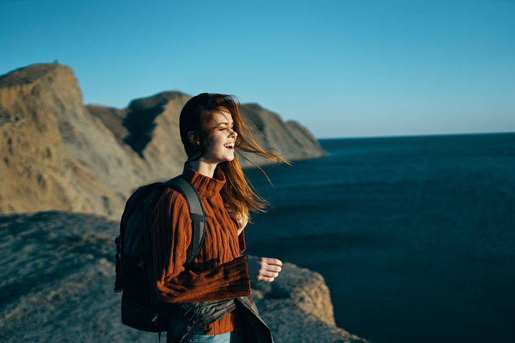Young woman looking away while standing on rock in sea against sky