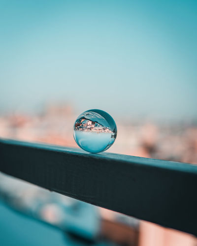 Close-up of crystal ball on railing