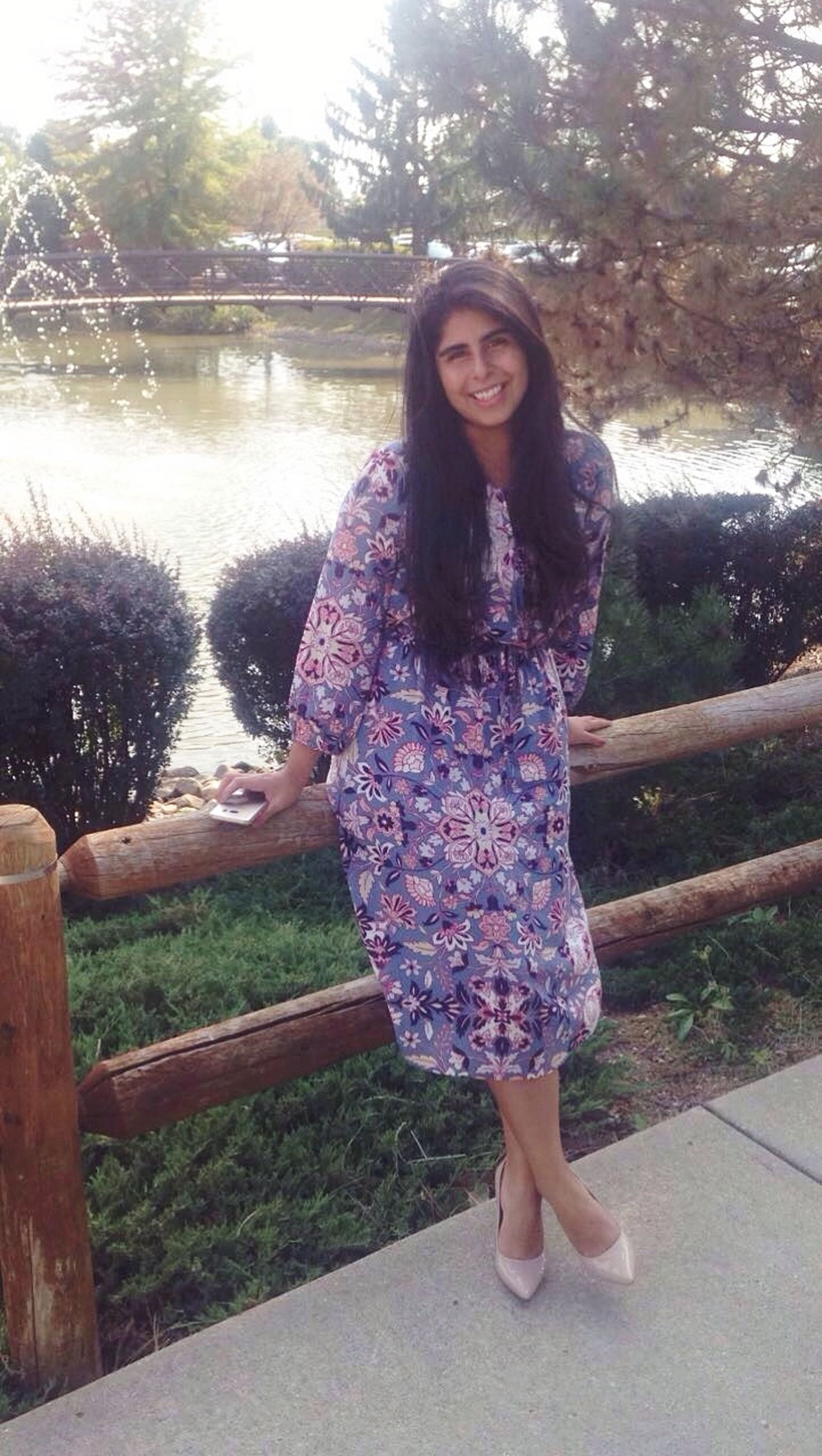 full length, one person, real people, leisure activity, young adult, smiling, young women, looking at camera, tree, casual clothing, beautiful woman, day, front view, happiness, lifestyles, outdoors, standing, portrait, park - man made space, nature, posing, growth, water