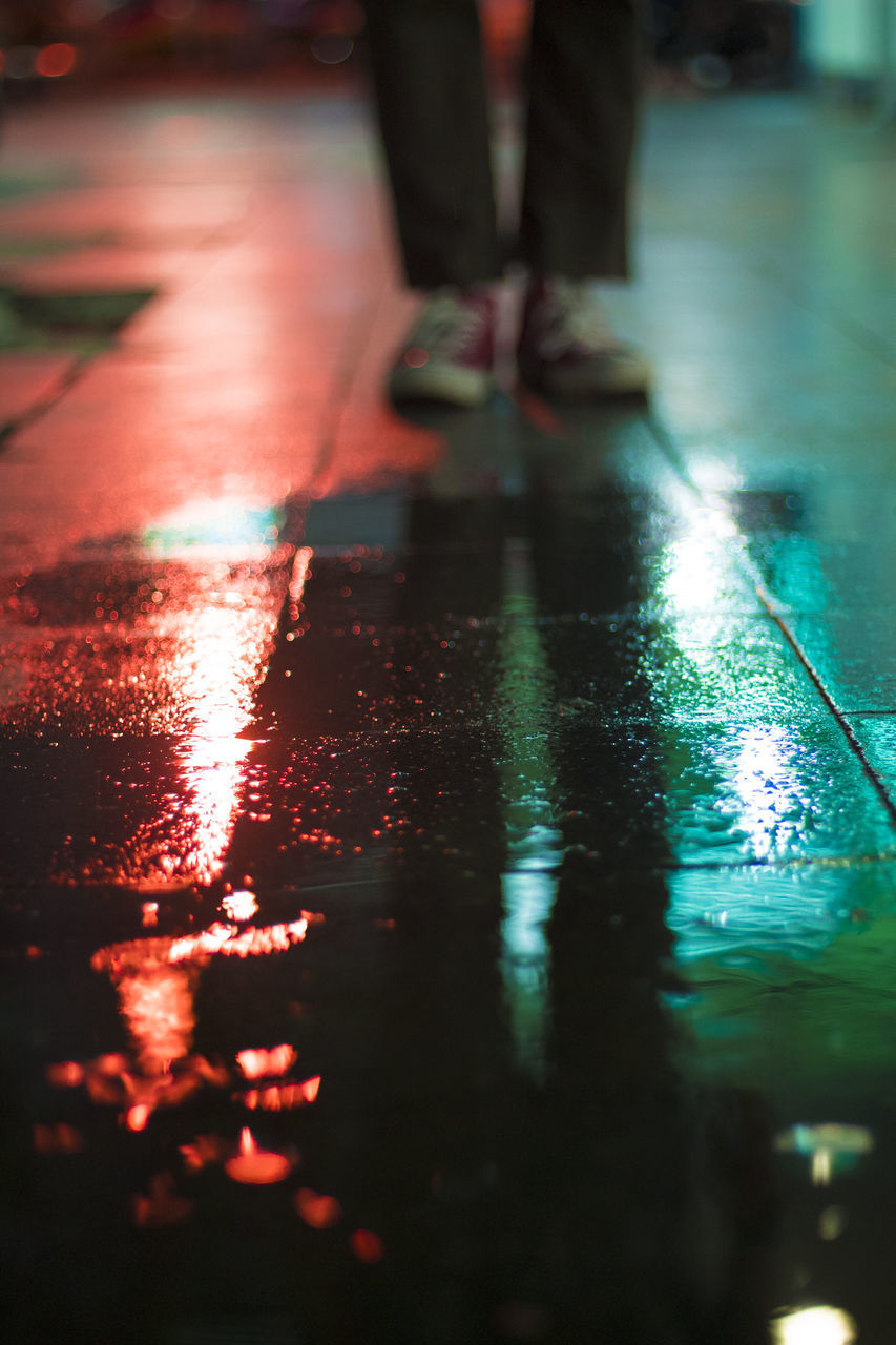 low section, human leg, one person, illuminated, human body part, body part, night, selective focus, wet, real people, city, flooring, street, standing, water, leisure activity, reflection, shoe, human foot, rain, surface level, human limb, tiled floor