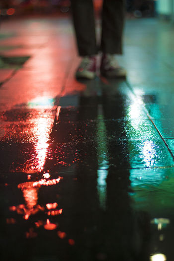 Low section of man standing on wet street at night