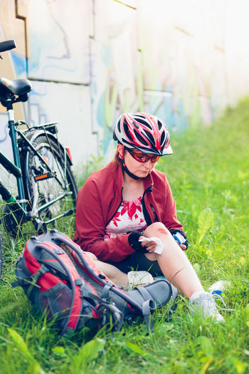 Woman dressing the wound on her knee with medicine in spray and gauze on bike trip on summer day Care Cyclist Medicine Vacations Woman Accident Active Activity Backpack Bandage Bicycle Bike Biker Dressing Hurt Injury Knee One Person Outdoor Pursuit Outdoors Person Real People Scratch Summer Wound