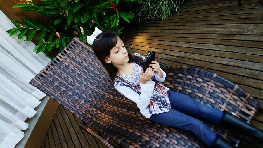 High angle view of girl using digital table while sitting on chair at home