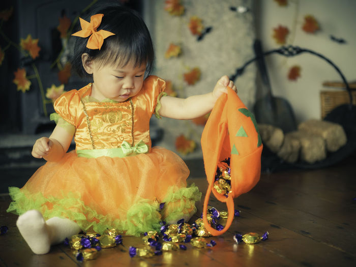 Baby girl holding jack o lantern basket with candies at home