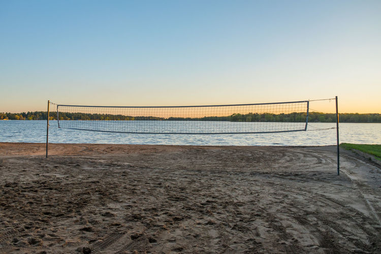 Volleyball Net on the Beach Sport Beach Volleyball Beach Net - Sports Equipment Team Sport Water Copy Space Sunset Sand No People Recreation  Isolated MidWest Lake Volleyball Net