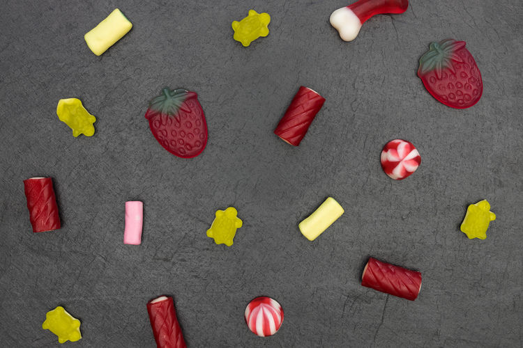 Candy sweets on dark background Multi Colored Candy Sweets Red Yellow Strawberry Sugar Minimal Food Abstract Dark Background Group Bunch Mixture  Overhead View Top View Tasty