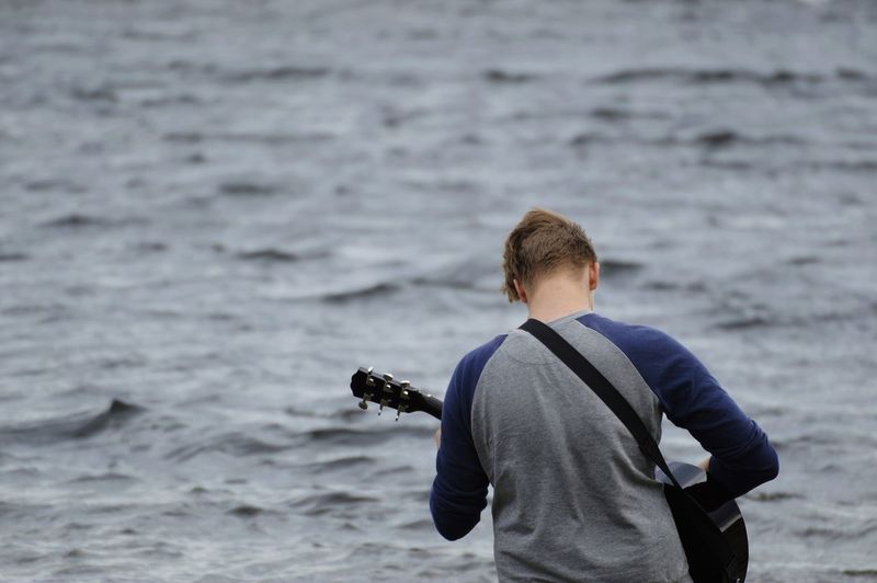 Rear View Of Teenage Boy Playing Guitar At Beach