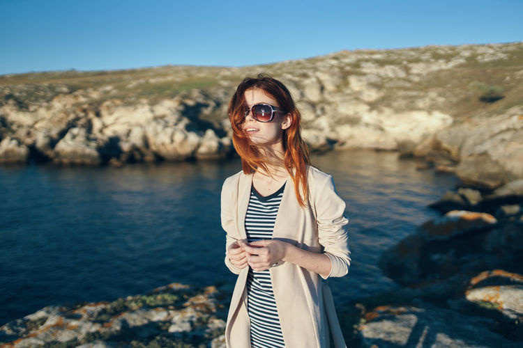 Woman wearing sunglasses standing on rock at shore