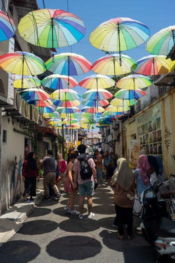 People walking on multi colored buildings in city
