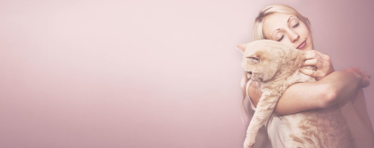 Panoramic Shot Of Young Woman Embracing Cat While Standing Against Pink Wall