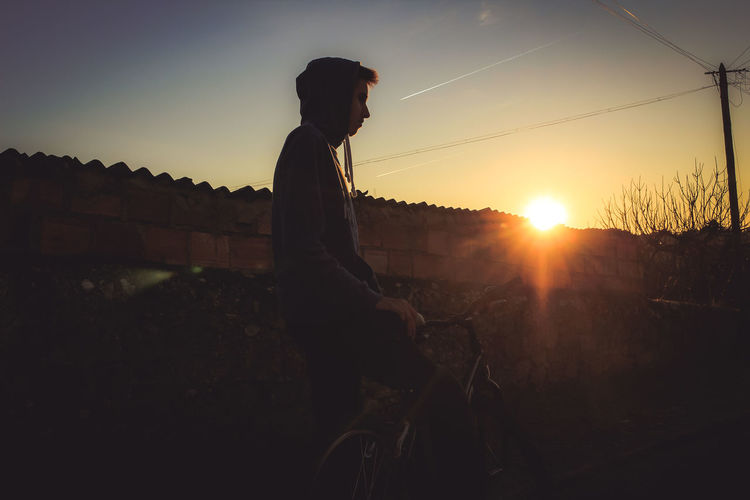 Side view of silhouette man riding bicycle against sunset sky