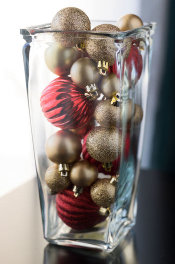 Close up of baubles on vase on table against white background