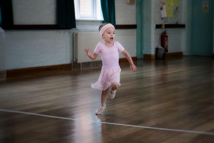 Girl wearing ballet shoe running in dance studio