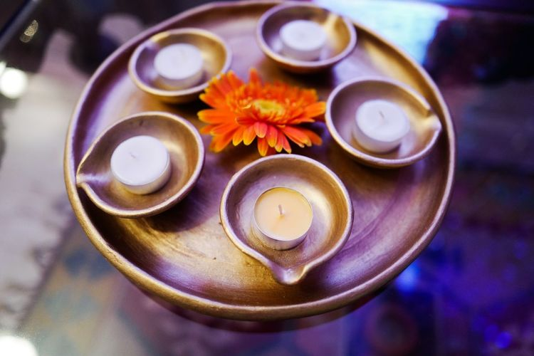 High Angle View Of Candles With Diyas And Flower In Plate