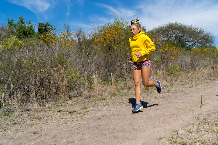 Woman running in the forrest. young blond woman running in the forrest on a warm summer day.