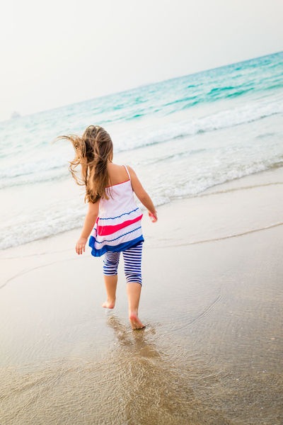 Running barefoot Beach Child Day Full Length Girl Horizon Over Water Israel Leisure Activity Lifestyles Motion Nature One Person Outdoors Real People Rear View Sand Scenics Sea Shore Vacations Walking Water Wave