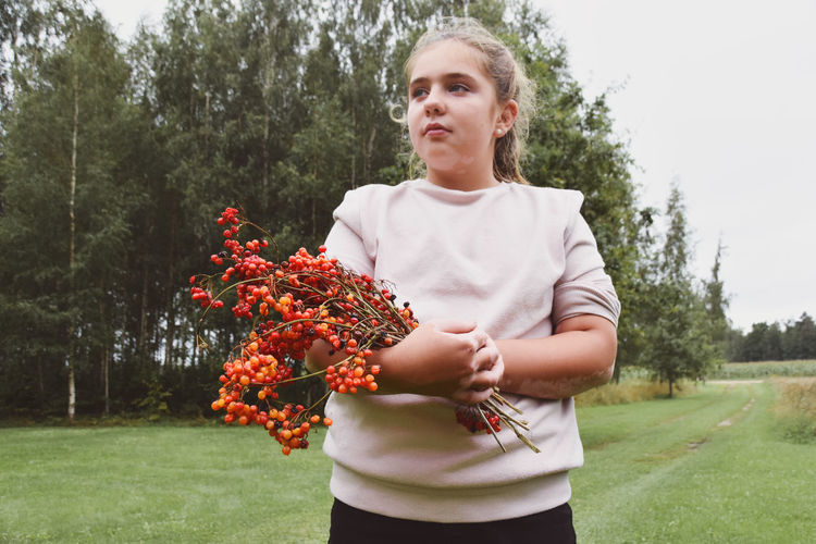 Teenage girl holding viburnum, autumn berries on rainy day, vitiligo on her arms visible.
