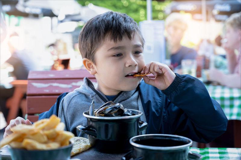 Full length of man eating food at restaurant