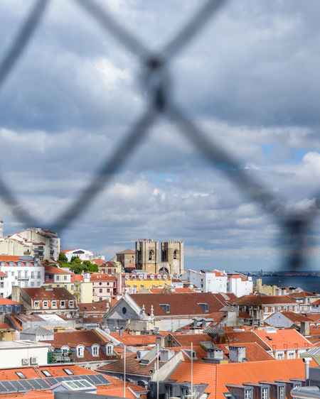 High angle view of townscape against sky through a fence