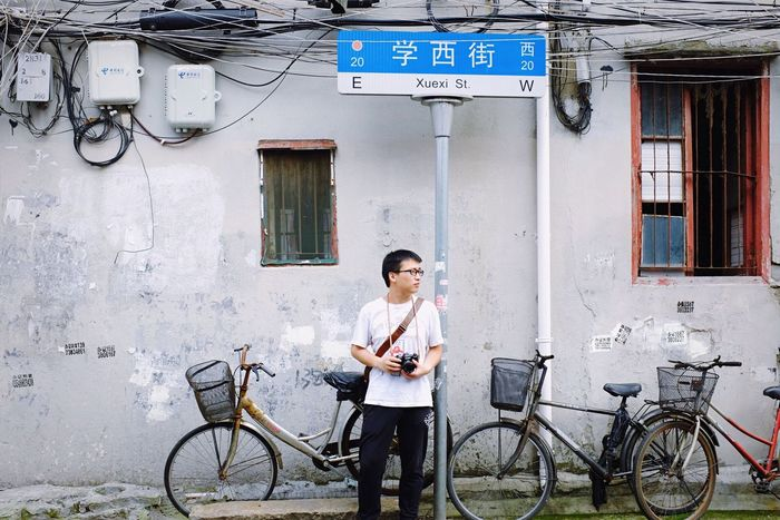 Bicycle Transportation Mode Of Transport Casual Clothing Communication Building Exterior Standing Day One Person Adults Only Architecture Young Adult Wireless Technology Outdoors City Full Length Adult People Phoyography Photographer The Week On Eyem Shanghai Streets Street Photography Streetphotography People Photography