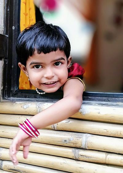 Portrait of cute girl at window