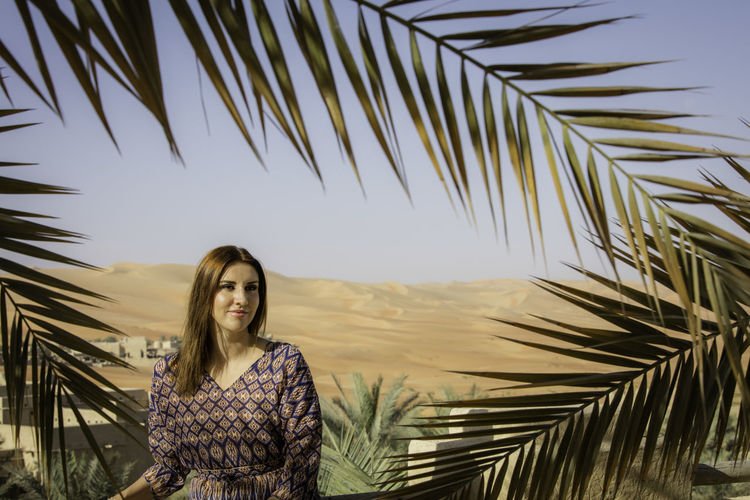 Thoughtful woman standing against desert