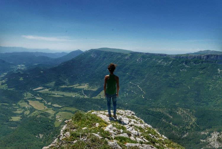 Rear view of man standing on mountain peak while looking at landscape against blue sky