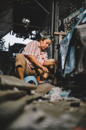 Senior woman working on wooden equipment