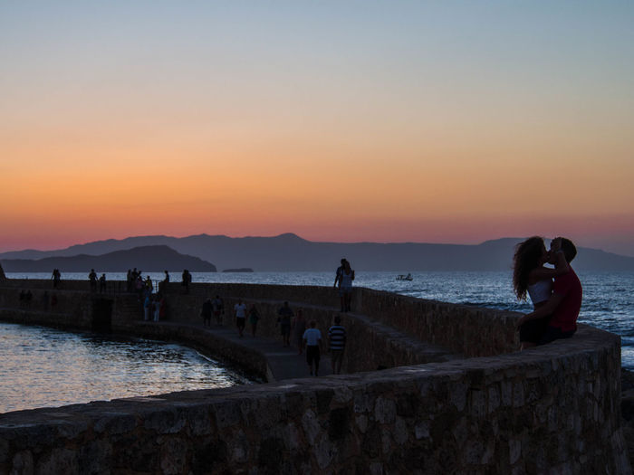 Couple kissing by sea against clear sky at dusk