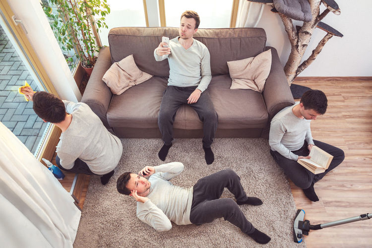 High angle view of friends relaxing on sofa at home