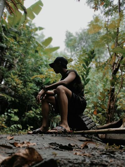 Full length of boy sitting in forest