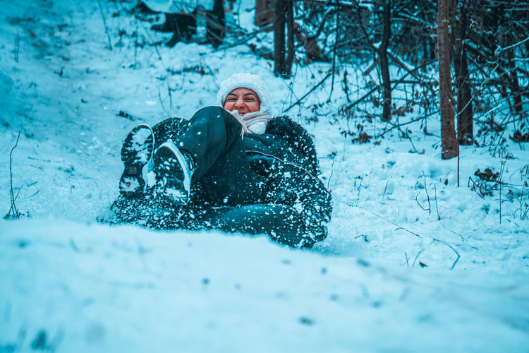 Full length of woman playing on snow covered land during winter