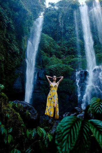 A woman in front of the Sekumpul waterfall on the island of Bali. Bali Arms Raised Beauty In Nature Flowing Water Forest Human Arm Land Long Exposure Motion Nature One Person Outdoors Plant Real People Scenics - Nature Sekumpul  Standing Water Waterfall Yellow Dress Young Adult Be Brave Moments Of Happiness 2018 In One Photograph