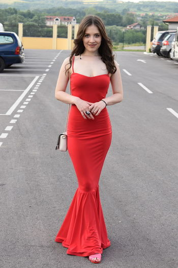 Portrait of woman in red dress standing on road at city