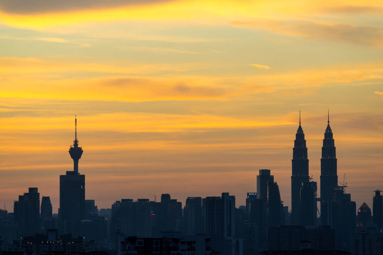 Petronas and kl tower in city against cloudy sky during sunset