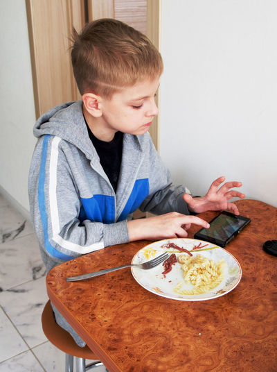 Blonde boy with phone Blonde Boy Bowl Boys Chair Childhood Day Eating Food Food And Drink Freshness Home Interior Indoors  Lifestyles Meal One Boy Only One Person People Phone Plate Ready-to-eat Real People Sitting Table
