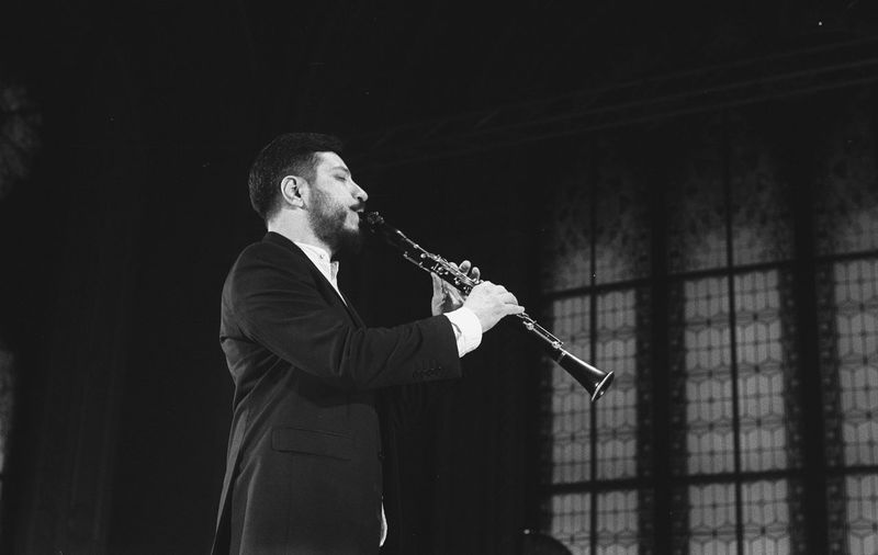 Man playing clarinet while standing at studio