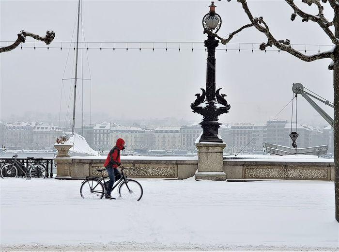 Man riding bicycle on street during winter