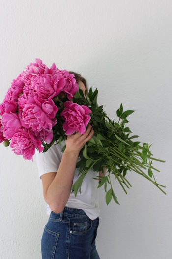 Midsection of woman holding pink flower against wall